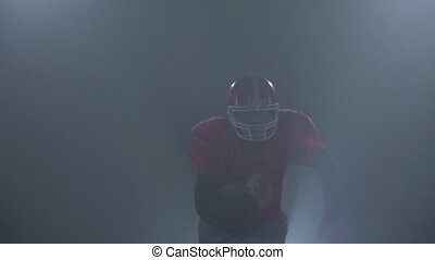 American football player runs on the camera. Smoky background studio