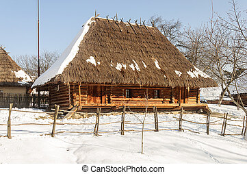 Old wooden peasant's house with straw roof - Old Ukrainian...