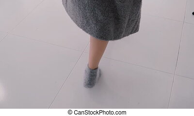 Close-up view to the woman in socks and long sweater walking...