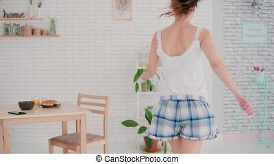 Happy young woman dancing in kitchen wearing pajamas in the...