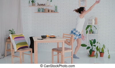 Funny young woman dancing in kitchen wearing pajamas in the...