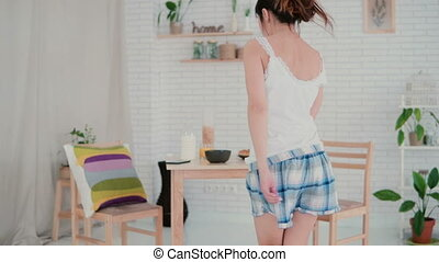 Beautiful young woman in kitchen dancing in the morning....