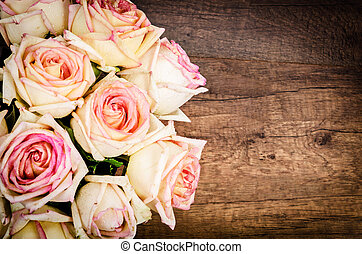 Bunch of pink roses against a wooden wall. - Bunch of pink...