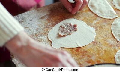 Woman prepares meat pies, working with the dough and...