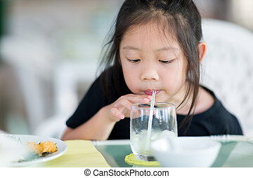 Asian Child Drinking Water Using Straw from Glass