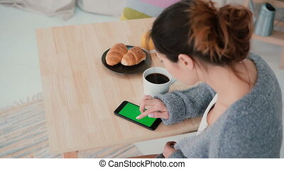 Young woman sitting at the table and drinking coffee in...