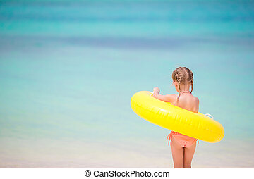 Adorable girl with inflatable rubber circle going to swim -...