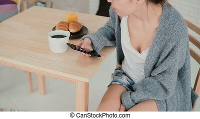 Young woman uses the smartphone during breakfast in a...