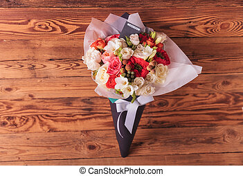 colorfull flowers bouquet in a cone with card and bow on a...
