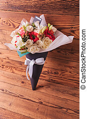 side view of a beautiful spring flowers bouquet on a wooden...