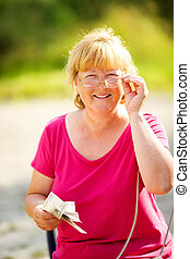 mature woman holding money and glasses outdoors