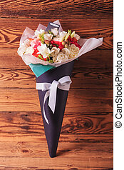 beautiful flowers arrangement in a cone with bow on old wood...