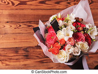 floral arrangement with a card for copy on old wood...