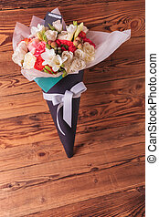 bunch of colorful spring flowers in a cone with bow on old...