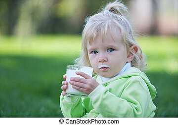 Milk moustache - A little girl dirty with milk is sitting in...