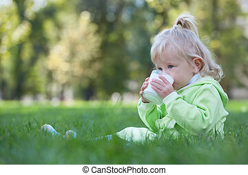 Serious little girl drinking milk - A serious toddler is...