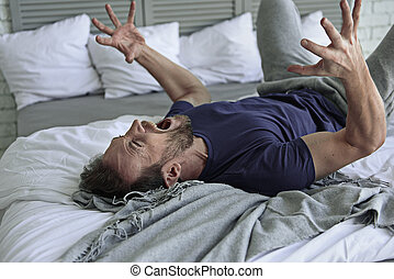 Depressed crying male person at bed - Upset man is loudly...