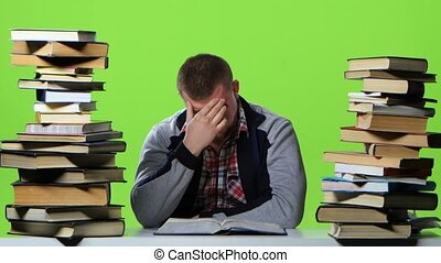 Man leafing through a textbook, it suffers from headaches....