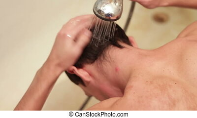 Water splash hitting on man's head. - Young man washing hair...