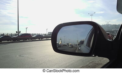 View in rear view mirror of city street traffic - Rearview...