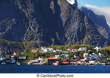 Norwegian fishing village with traditional red rorbu huts,...