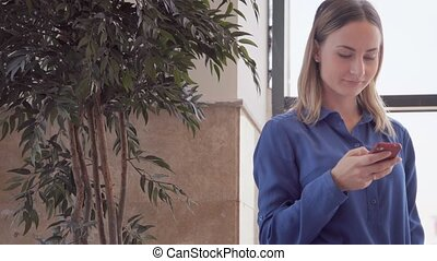Happy young woman using smart phone in shopping mall. -...