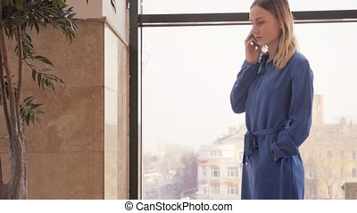 Young Girl is Talking on the Mobile Phone in Shopping Mall