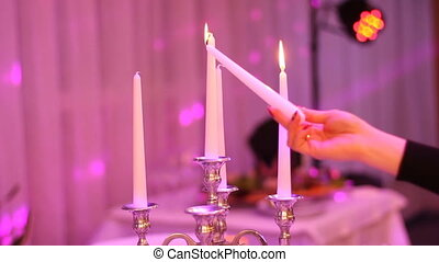 Woman hand burns candles in a chandelier on elegant dinner table