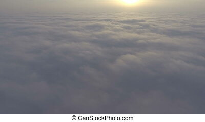 Flight over field of clouds in sunrise time.