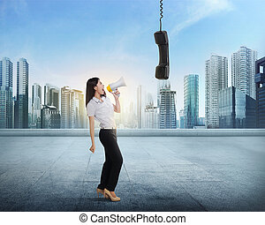 Beautiful asian business woman with bullhorn screaming to...