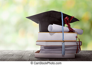 Graduation hat with degree paper on a stack of book