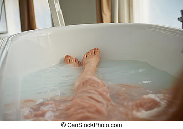 Legs resting in the tub of a person. Cleopatra bath with milk. Beauty and relaxation