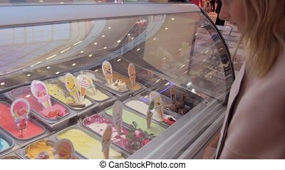 the girl chooses a ice cream at the window.
