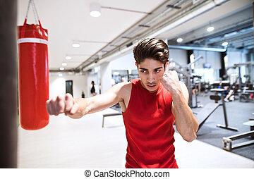 Fit hispanic man in gym punching boxing bag - Fit hispanic...