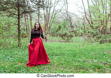witch in the woods with a candle - mystical witch woman in a...