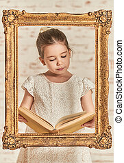 Adorable young little girl reading a book - Indoor portrait...