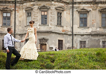 Gorgeous lady in evening gown walks down on the green hill