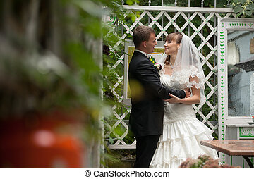 Bride looks in groom's eyes with love while they stand on the porch