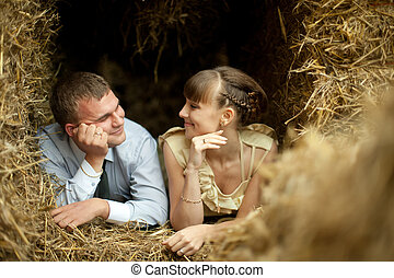 Thoughtful husband looks at his wife lying on the hay