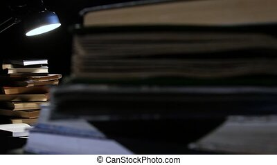 Girl leafing through a book and falling asleep at the table. Black background