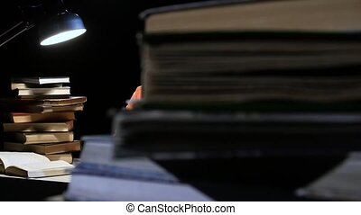Girl reads and writes information in a notebook. Black...