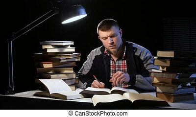 Man reading a book and writes in a notebook. Black...