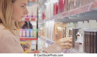 Young woman with braid chooses perfume in small shop.