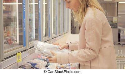 girl chooses frozen foods in supermarket