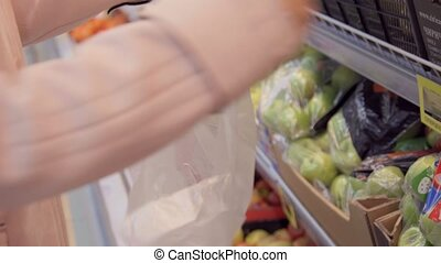 Woman selecting fresh red apples in grocery store produce...
