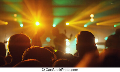 People crowd partying at rock concert in a night club. -...