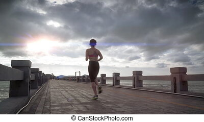 Sport girl is running on the beach in early moning with sun