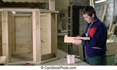 Carpenter applying glue on wooden plank with brush -...