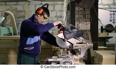 Carpenter cutting wood with sliding mitre saw - Joiner...