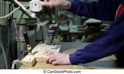 Master drilling holes with wood cutter in board - Closeup...